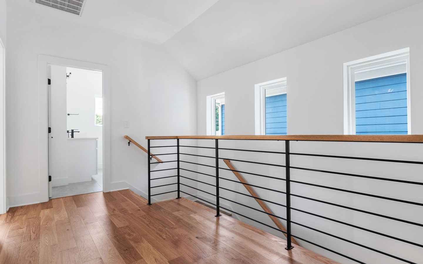 inside a freshly renovated home, showing stair railings and door open to bathroom